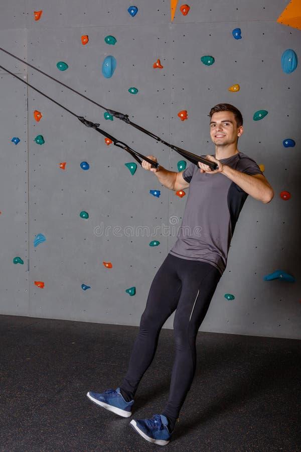 Un individuo es atleta, se tira para arriba en bandas y sonríe Contra la pared para subir foto de archivo