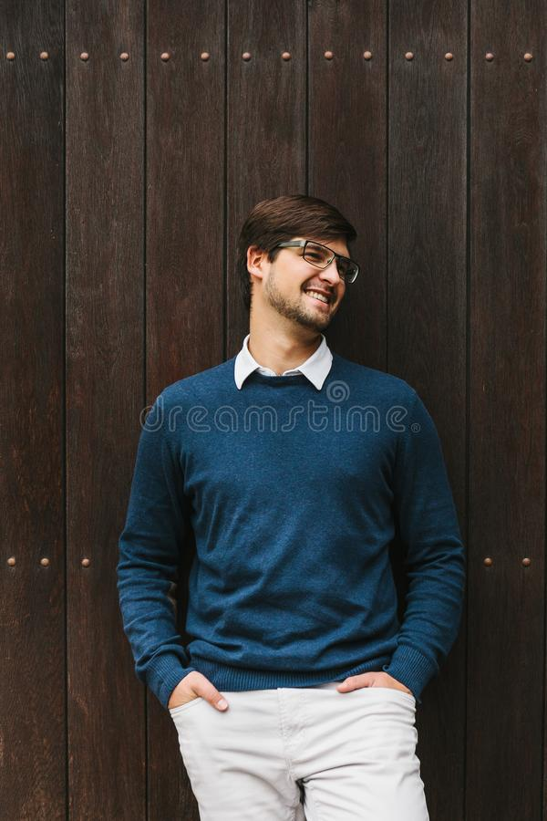 Un individuo europeo elegante joven se coloca y sonríe al lado de una pared de madera imagen de archivo libre de regalías