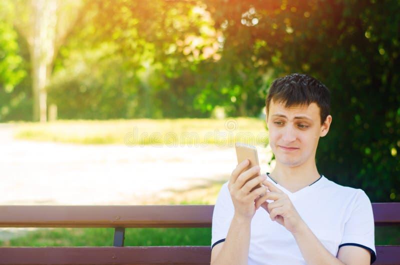 Un individuo europeo joven se sienta en un banco en un parque de la ciudad y hace una cara divertida que mira en el teléfono El c fotografía de archivo