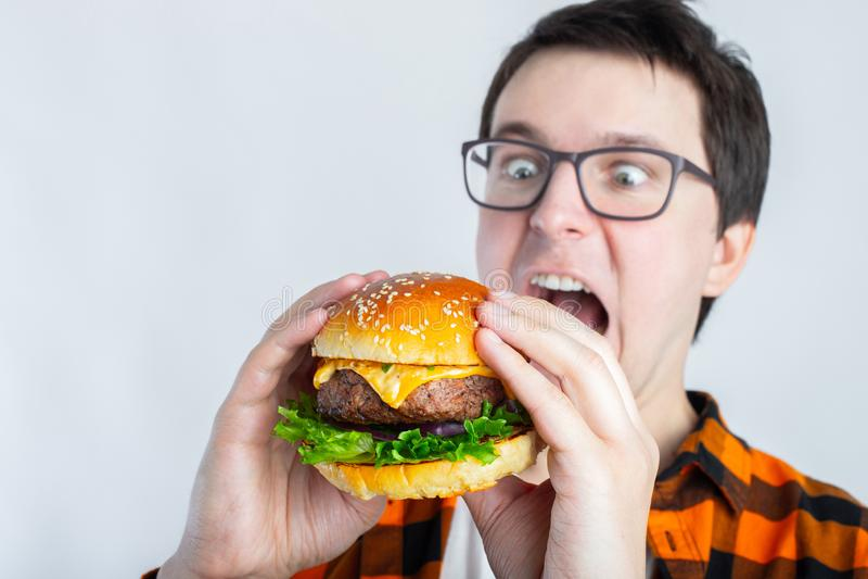 Un individuo joven con los vidrios que sostienen una hamburguesa fresca Un s muy hambriento imagen de archivo libre de regalías