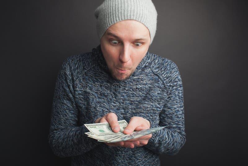 Un individuo joven en un casquillo gris y una barba, sosteniendo una pila de dinero y de miradas fijas en ella en un fondo negro  foto de archivo libre de regalías