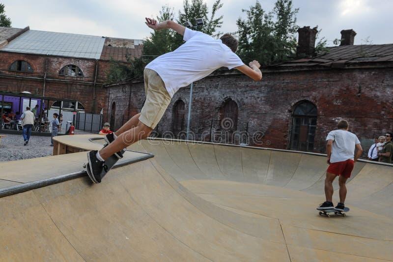 Un individuo joven en un monopatín en una camiseta blanca con el suyo detrás en una plataforma especialmente equipada en el movim imágenes de archivo libres de regalías