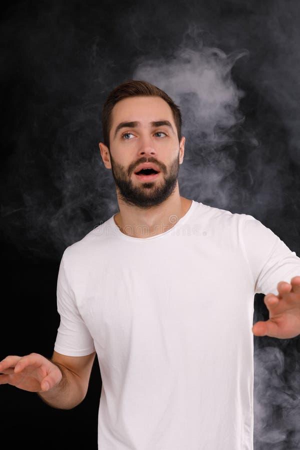 Un individuo joven en una camiseta blanca en un fondo negro con miradas del humo al lado fotos de archivo libres de regalías