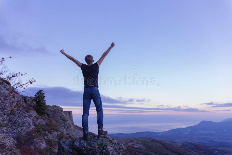 Un individuo joven en una camiseta negra se está colocando encima de una montaña, separándose los brazos hacia el cielo imágenes de archivo libres de regalías