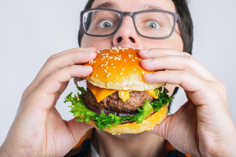 Un individuo joven está sosteniendo una hamburguesa fresca Un estudiante muy hambriento come los alimentos de preparación rápida  imagen de archivo libre de regalías