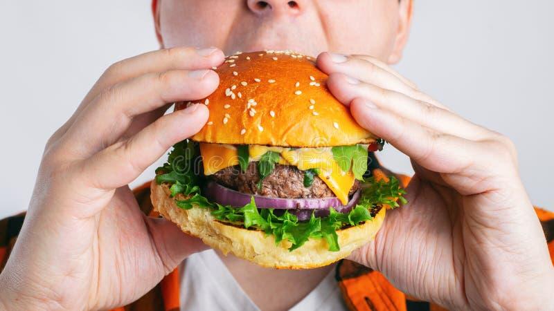 Un individuo joven está sosteniendo una hamburguesa fresca Un estudiante muy hambriento come los alimentos de preparación rápida  foto de archivo libre de regalías