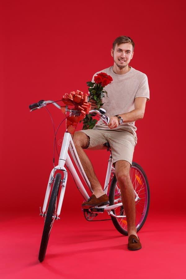 Un individuo joven que se sienta en una bicicleta que quiere dar, con las flores en sus manos fotografía de archivo
