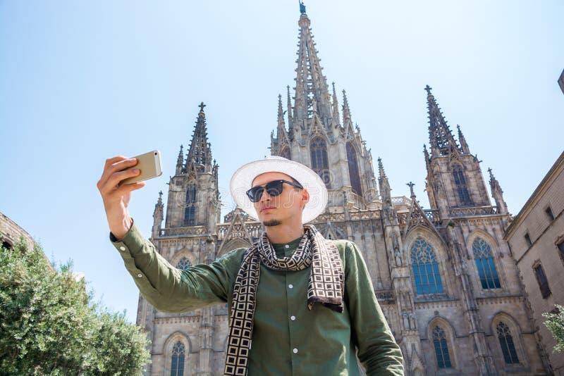 Un individuo joven, turista, hace el selfie delante de la fachada de T fotografía de archivo