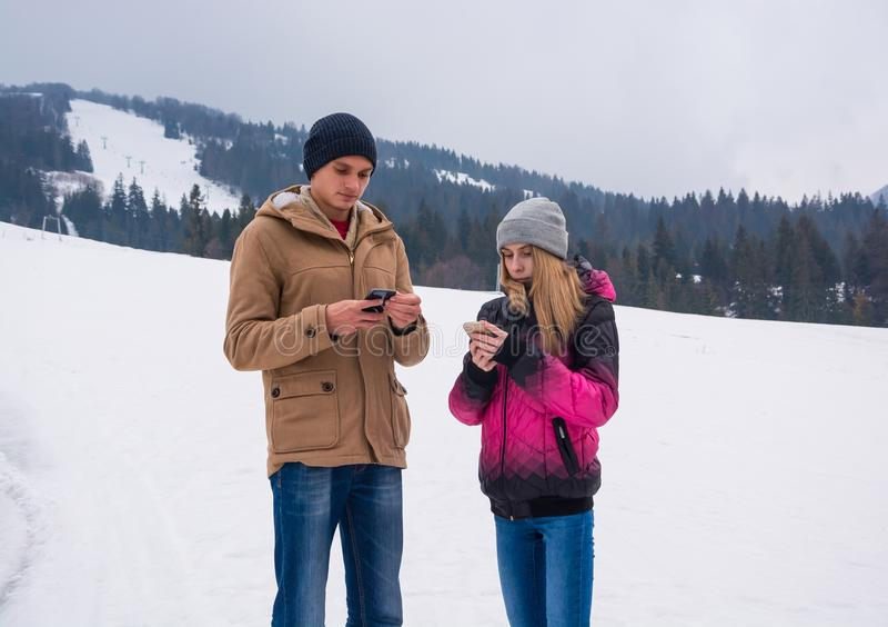 Un individuo joven y una muchacha que miran sus smartphones contra fotos de archivo