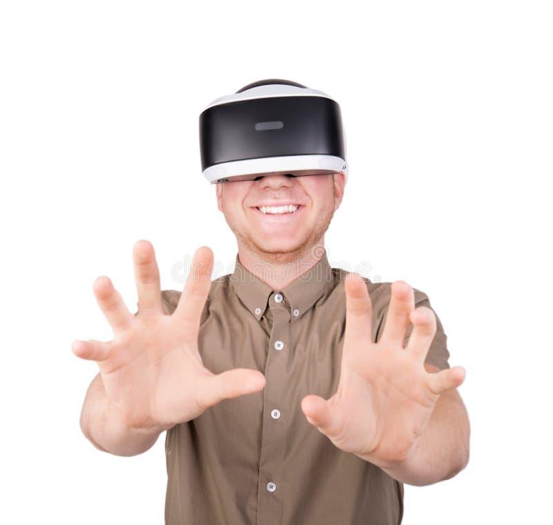Un individuo que intenta tocar o abrazar con los objetos virtuales de las manos en una simulación digital Un hombre joven en vidr fotos de archivo