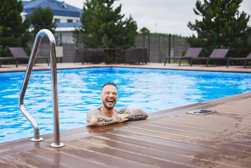 Un individuo sonriente brutal joven hermoso del hombre, elegante y de moda que presenta en la piscina al aire libre fotos de archivo libres de regalías