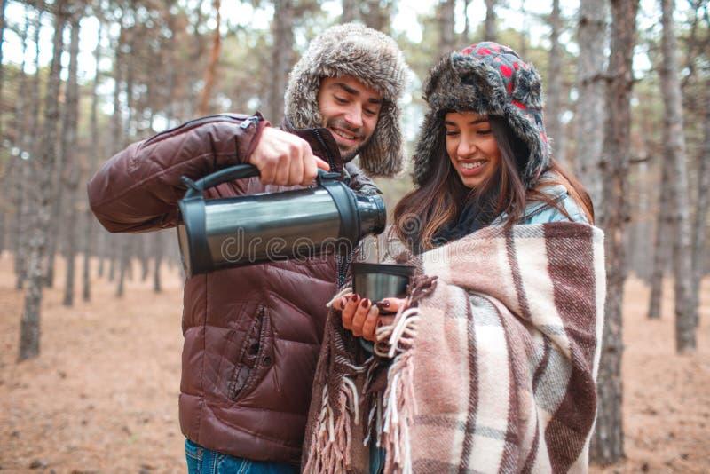 Un individuo vierte el té caliente para una muchacha de un termo en una taza en el bosque del otoño imagenes de archivo
