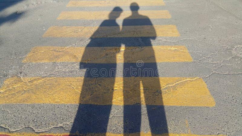 Un individuo y un soporte de la muchacha al principio de un paso de peatones, donde se escribe la parada y espera el paso del tie fotografía de archivo libre de regalías