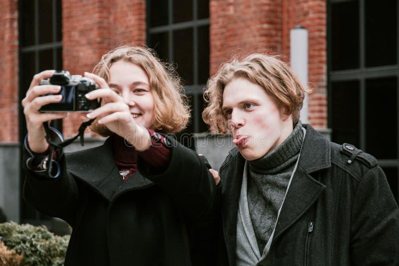Un individuo y una muchacha tomar imágenes de ellos mismos y hacer caras divertidas fotografía de archivo libre de regalías