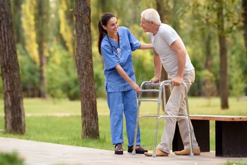 Un infermiere aiuta un pensionato a camminare nel parco sui trampoli adulti fotografia stock