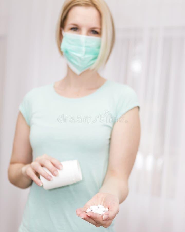 Un infermiere dà una compressa in una maschera di salute immagini stock