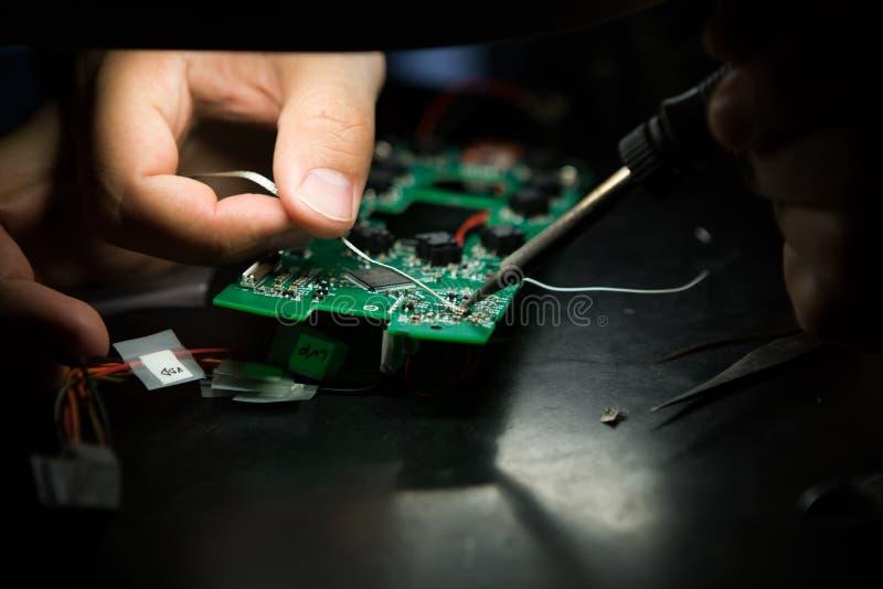 Un ingénieur travaille à un appareil électronique image libre de droits