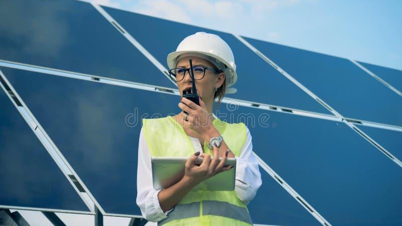 Un ingénieur travaille avec des dispositifs, se tenant sur un toit près des batteries solaires Alternative, concept vert d'énergi images stock