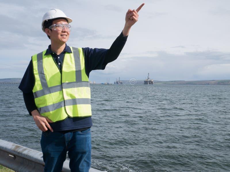 Un ingeniero asiático que señala y que se coloca delante semi de submers imágenes de archivo libres de regalías