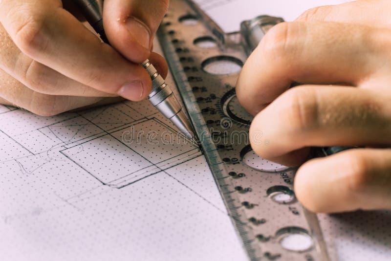 Un ingeniero joven aprende trabajar con los dibujos fotos de archivo libres de regalías