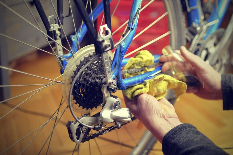 Un ingranaggio e una catena Lubrificazione e riparazione dell'azionamento della bicicletta Manutenzione della bici prima della gu fotografia stock