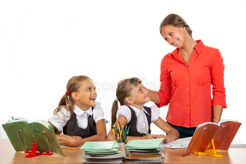 Un insegnante gentile comunica con gli studenti seduti a una scrivania immagini stock libere da diritti
