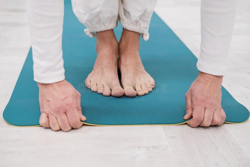 Un insegnante maschio e un istruttore in vestiti bianchi stanno presentando un giallo e una stuoia blu di yoga, preparanti per un fotografia stock