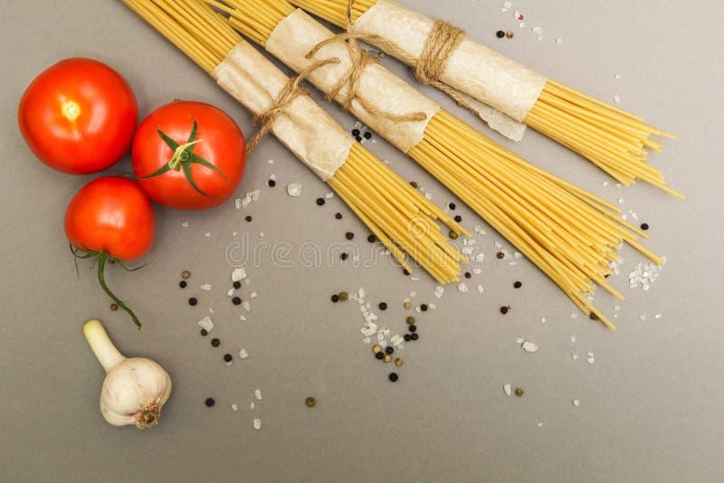 Un insieme degli ingredienti per la cottura della pasta su un fondo grigio, vista superiore immagine stock libera da diritti
