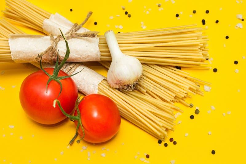 Un insieme degli ingredienti per pasta su un fondo giallo, vista superiore immagine stock