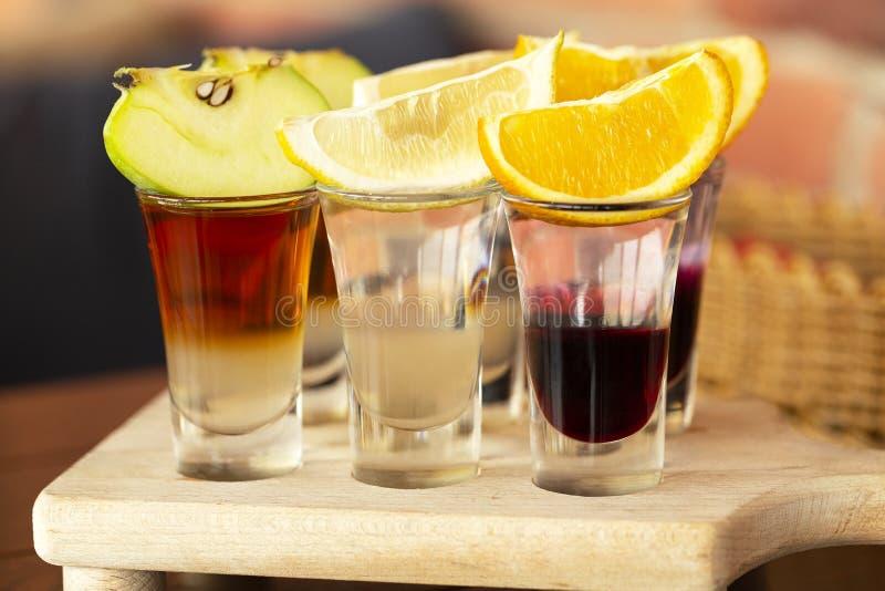 Un insieme dei cocktail stratificati nei tiratori di vetro con frutta come spuntino per fotografia stock libera da diritti