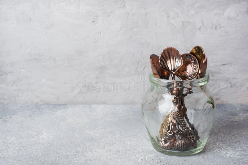Un insieme dei cucchiaini differenti in un barattolo di vetro Fondo grigio con lo spazio della copia immagini stock libere da diritti