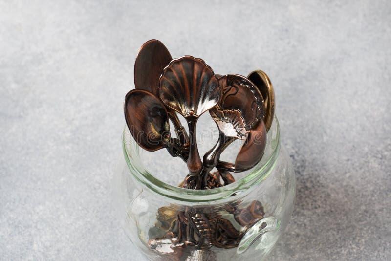 Un insieme dei cucchiaini differenti in un barattolo di vetro Fondo grigio con lo spazio della copia fotografie stock libere da diritti