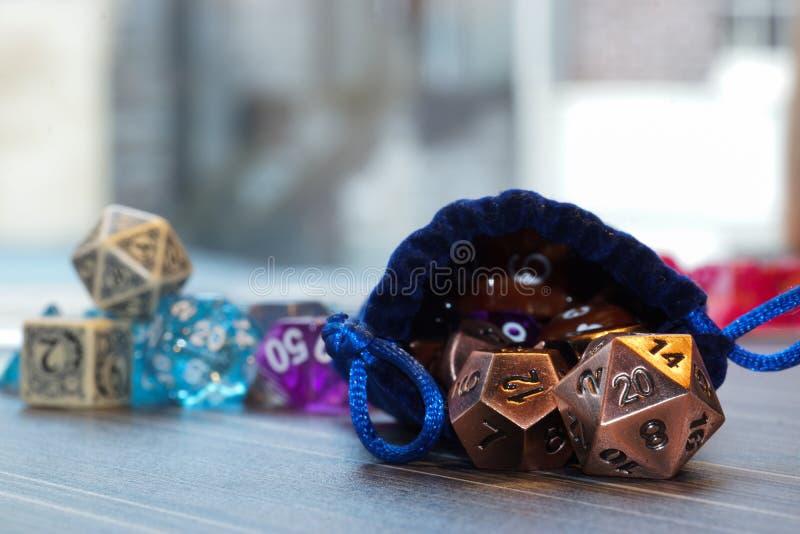 Un insieme dei dadi polyhedral con una borsa di corda di tiraggio immagine stock