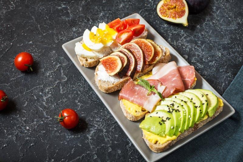 Un insieme dei panini dell'avocado, dei pomodori ciliegia e delle uova, fichi, prochutto su un fondo di pietra immagini stock libere da diritti