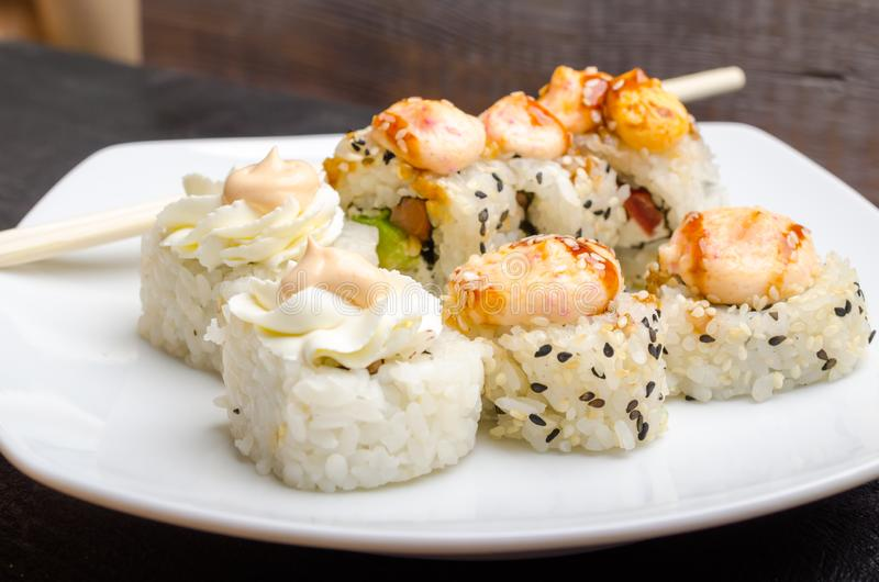 Un insieme dei rotoli di sushi giapponesi tagliati su un primo piano bianco del piatto fotografia stock