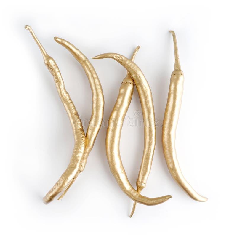 Un insieme del peperoncino rosso dorato peperoncino fatto da oro Isolato su priorità bassa bianca fotografie stock