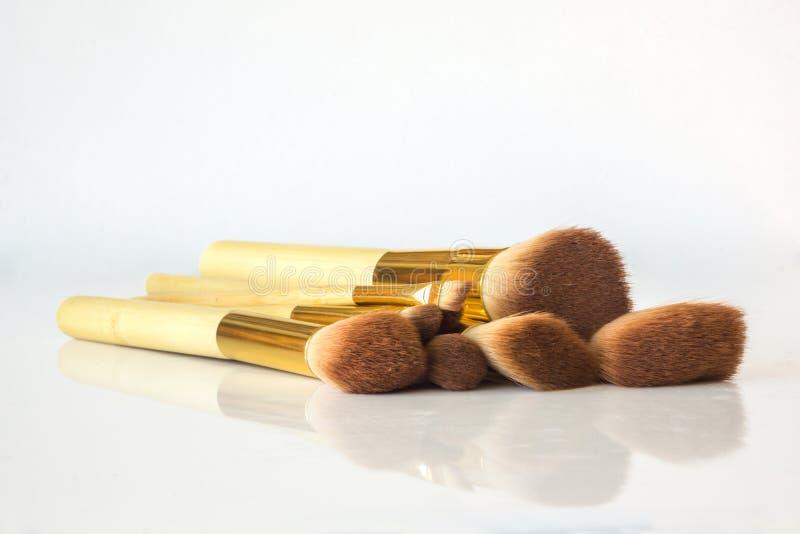 Un insieme del primo piano delle spazzole professionali di trucco con una riflessione fotografia stock