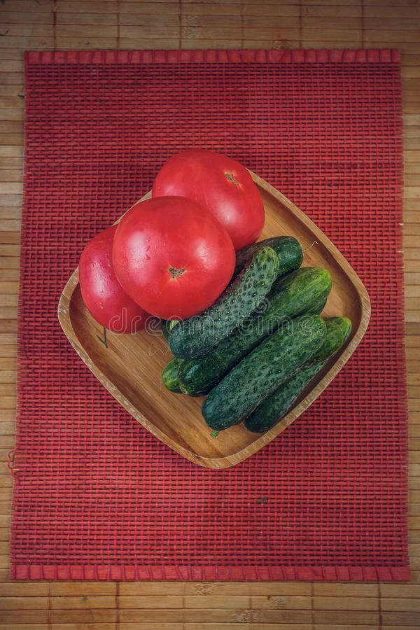 Un insieme della verdura fresca dei cetrioli e dei pomodori su un piatto di bambù immagini stock