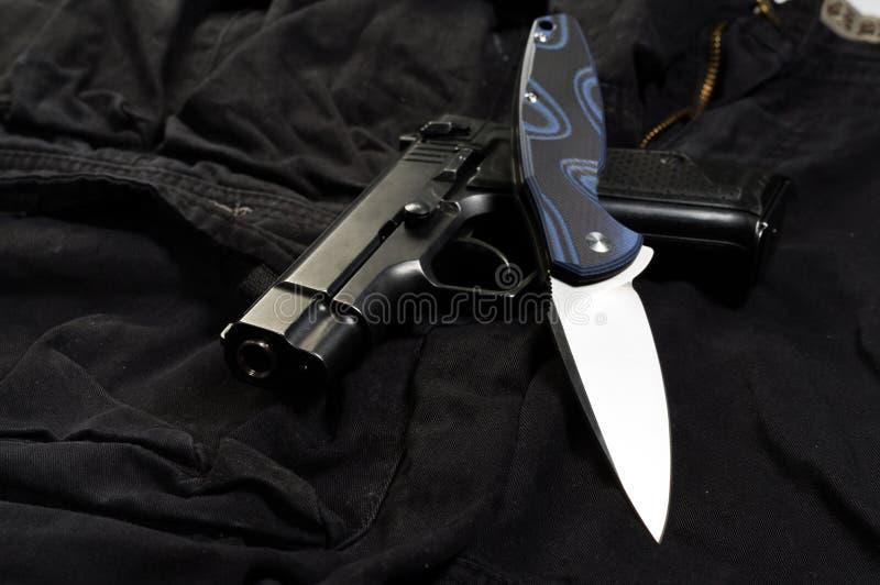 Un insieme delle armi da un coltello e da una pistola Lama di coltello bianca e pistola nera fotografia stock libera da diritti