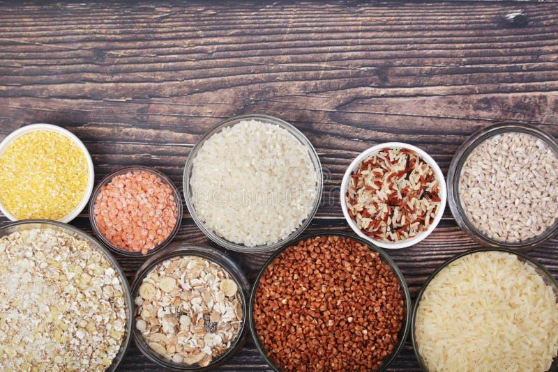 Un insieme delle ciotole riempite con differenti semi: grano saraceno, aumento, mais e farina d'avena fotografia stock libera da diritti