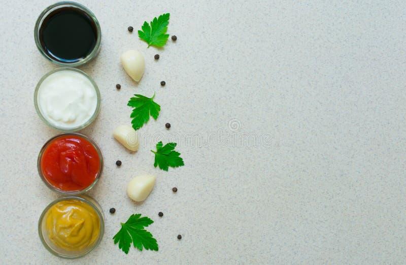 Un insieme delle salse e degli speciali Pepe, aglio, paprica, curry, prezzemolo, basilico, senape, noce moscata, curcuma Vista da immagini stock libere da diritti