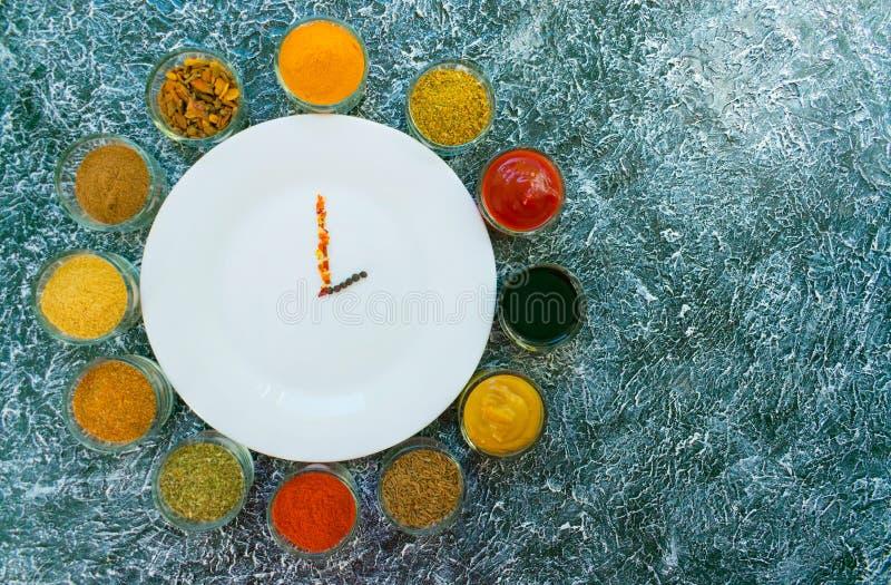 Un insieme delle spezie e le salse sono presentati intorno ad un piatto vuoto bianco sotto forma di orologio Pepe, sale, paprica, immagine stock