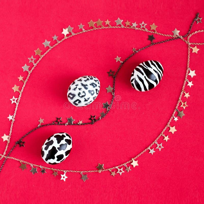 Un insieme delle uova di Pasqua dipinte come una zebra, una mucca, un leopardo delle nevi su un fondo rosso con oro, le catene d' immagine stock