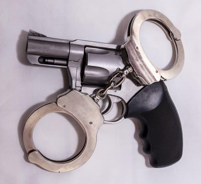 Un insieme di argento, manette del metallo sopra un revolver caricato di 357 magnum fotografie stock