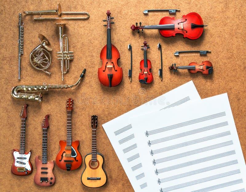Un insieme di quattro chitarre, di cinque strumenti musicali dell'orchestra della corda quattro e del vento d'ottone dorato fotografia stock libera da diritti