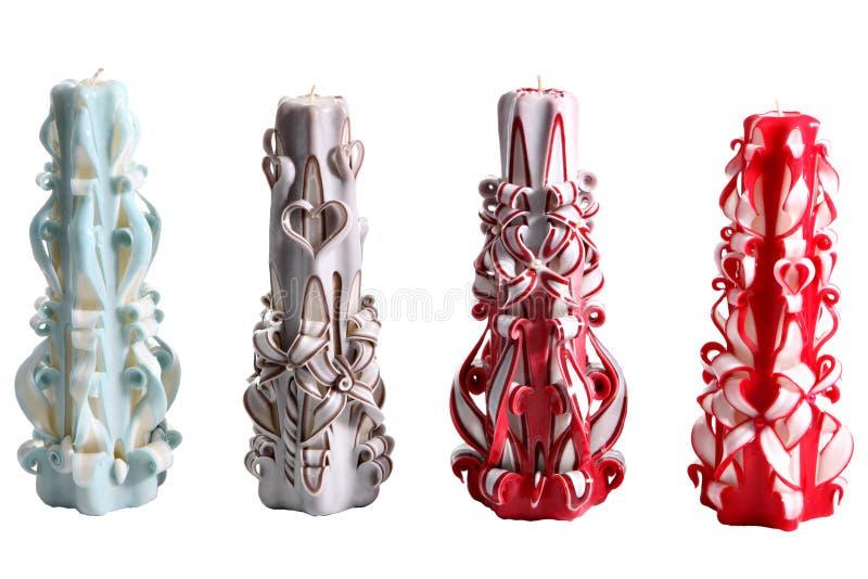 Un insieme di quattro scolpite di fatte a mano delle candele variopinte della cera, su bianco fotografie stock libere da diritti