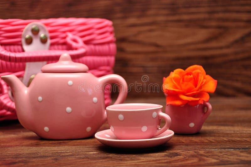 Un insieme di tè macchiato porcellana con un canestro rosa e una rosa arancio fotografia stock libera da diritti