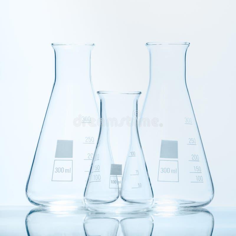 Un insieme di tre boccette coniche resistenti di temperatura vuota per le misure fotografia stock