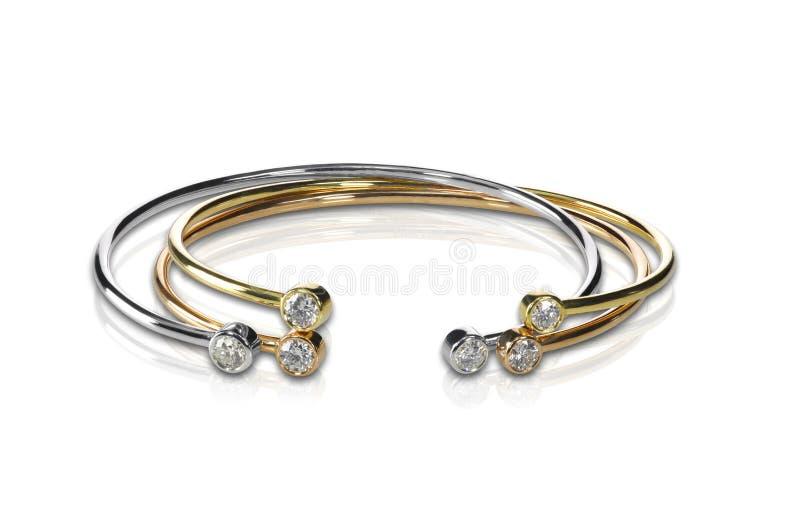 Un insieme di tre ha colorato i braccialetti del diamante e dell'oro impilati immagini stock