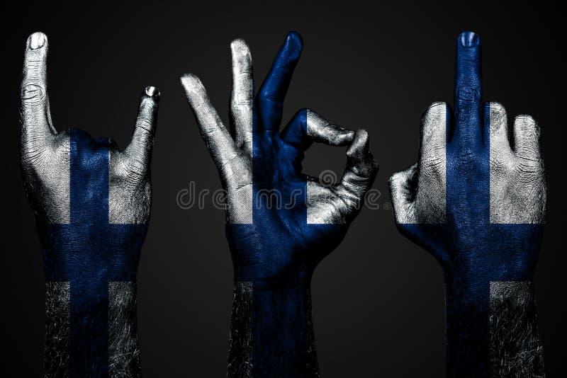 Un insieme di tre mani con un dito medio dipinto di manifestazione della Finlandia della bandiera, capra ed approvazione, un segn immagine stock